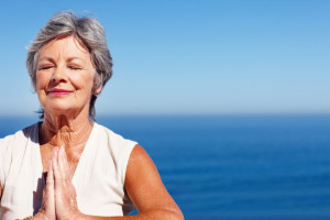 Closeup of senior woman doing yoga with ocean in background - copyspace
